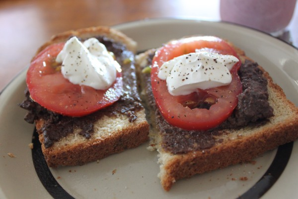 Chicken liver pate on whole grain bread, topped with fresh sliced tomatoes, sour cream and salt and pepper