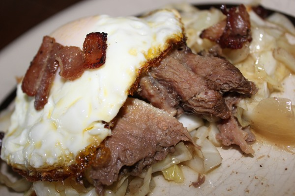 Shredded beef tongue on a bed of sauteed cabbage, topped with an over-medium egg and crispy bacon